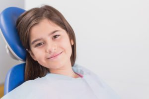 Smiling young patient sitting in dentists chair in dental clinic